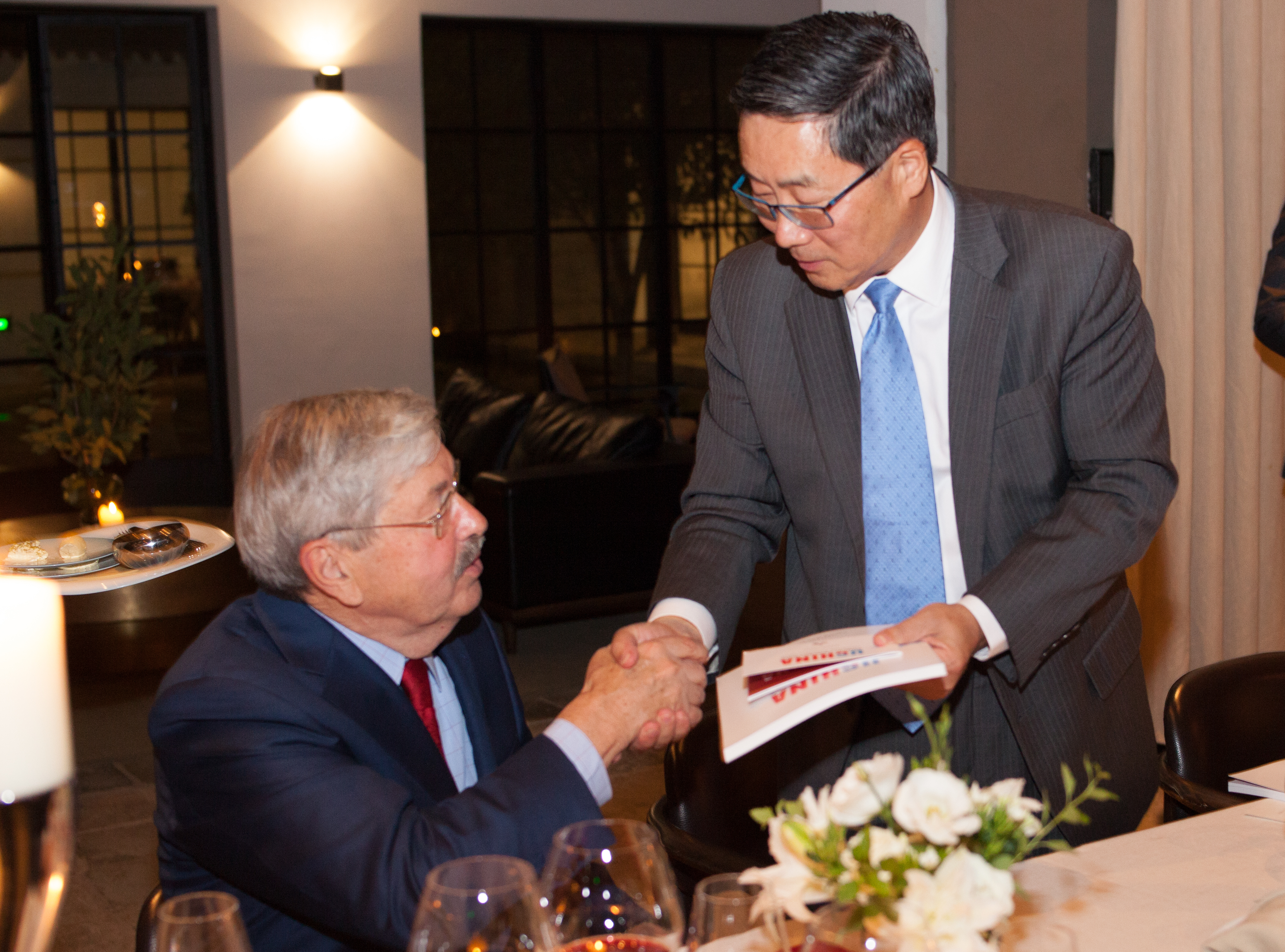 Dazong Wang and Ambassador Branstad shaking hands, giving survey