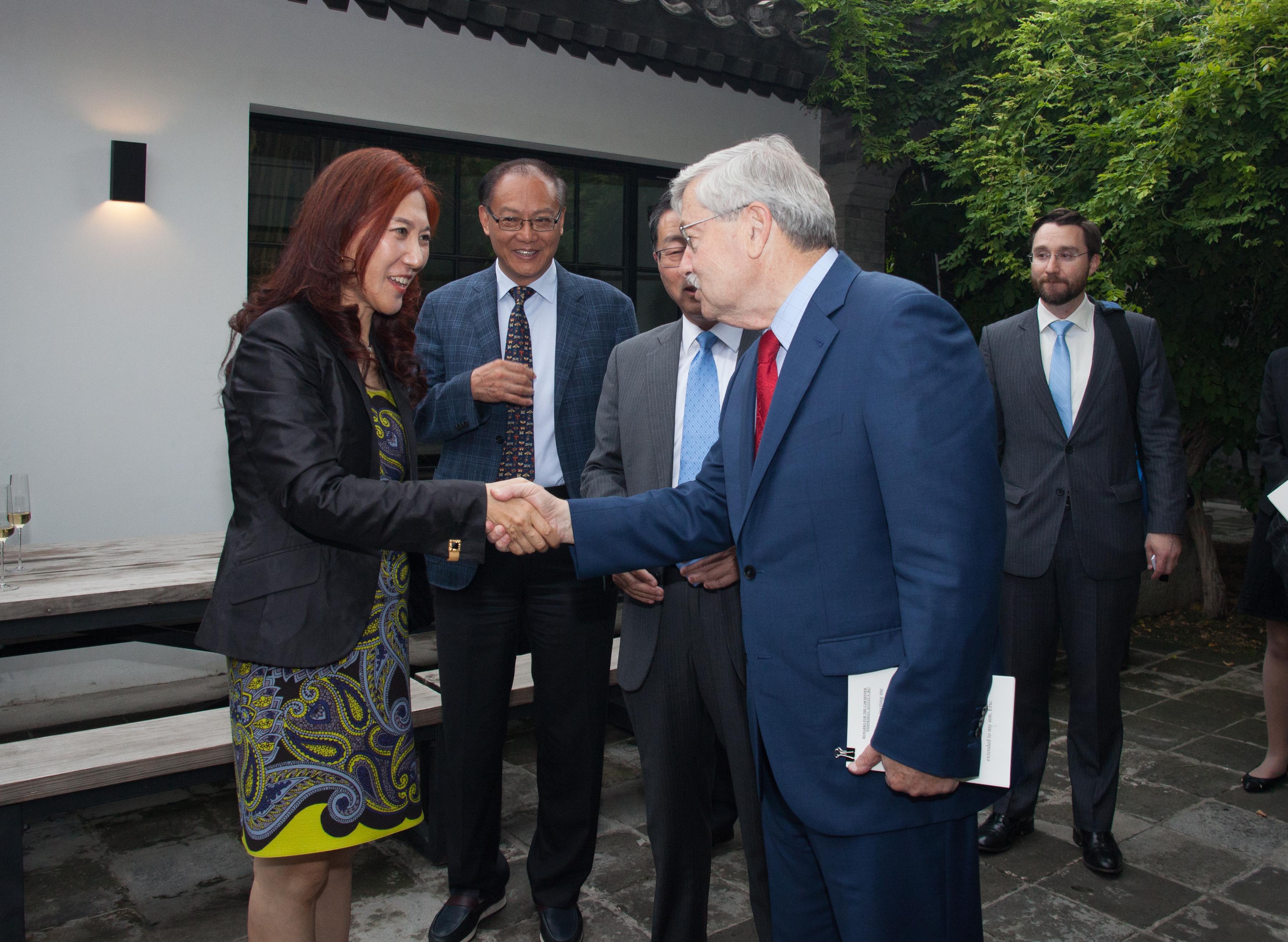 Wei Sun Christianson and Ambassador Branstad shaking hands